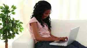 stock-footage-smiling-woman-typing-on-a-laptop-in-the-living-room