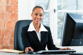 Businesswoman sitting at desk working on computer